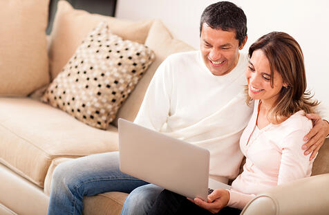 Couple at home going online on a laptop computer-1